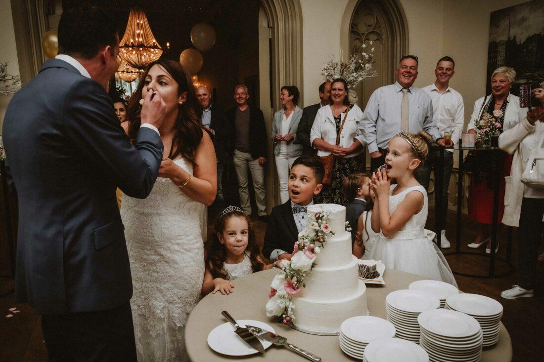 Kinderen kijken toe hoe bruidspaar elkaar cake voert